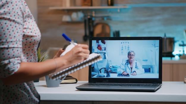 Dame die notities schrijft tijdens online medisch consult, luisterende vrouw arts zit achter laptop in de keuken. zieke persoon die tijdens videoconferentie over symptomen en behandeling bespreekt.
