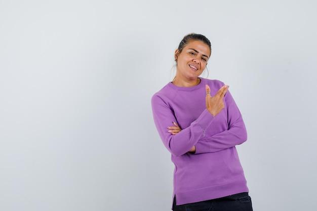 Dame die omhoog wijst in wollen blouse en er vrolijk uitziet