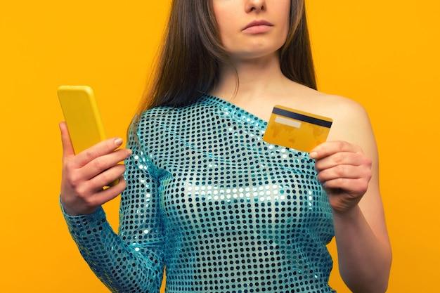 Dame die online met een creditcard en slimme telefoon op gele achtergrond koopt