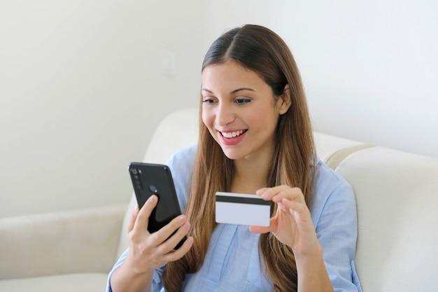 Dame die online met een creditcard en slimme telefoonzitting kopen ontspannen thuis op een laag in haar woonkamer
