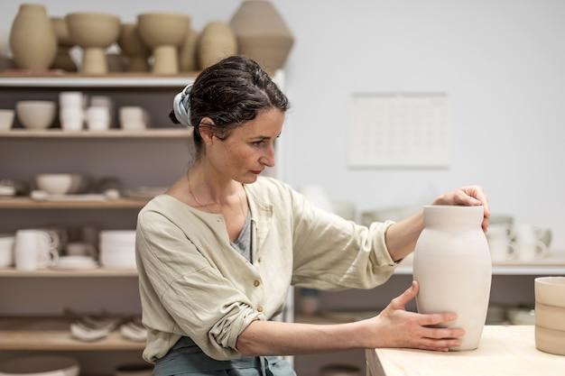 Dame die op bank met aardewerkwiel situeert en kleipot maakt