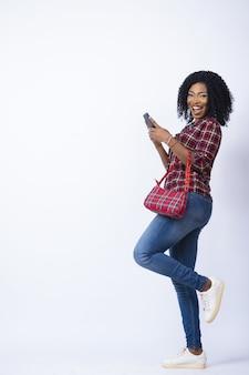 Dame die opgewonden en gelukkig kijkt met haar telefoon, met een handtas.