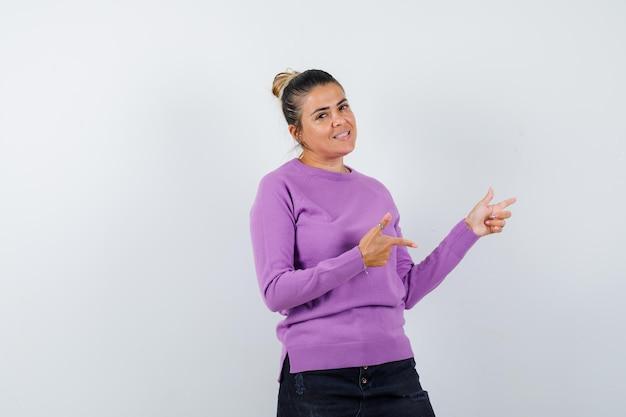 Dame die opzij wijst in wollen blouse en er vrolijk uitziet