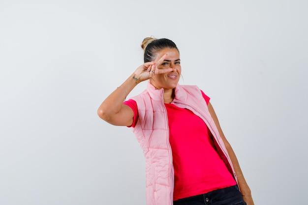 Dame die overwinningsteken op oog in t-shirt, vest toont en gelukkig kijkt