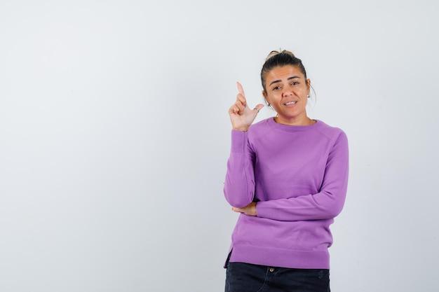 Dame die pistoolgebaar in wollen blouse toont en er vrolijk uitziet