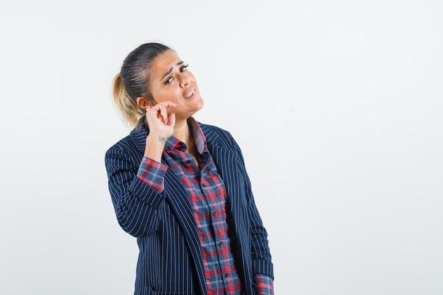 Dame die problemen heeft met hoorzitting in overhemd, jasje en verward, vooraanzicht kijkt.