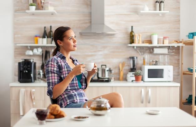 Dame die tijdens het ontbijt in de keuken geniet van een hete groene thee die uit een porseleinen kopje nipt