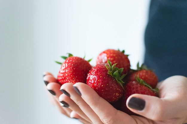 Dame die verse rijpe aardbeien in haar handen houdt