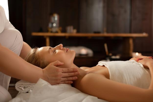 Dame die vredig ligt. jonge mooie vrouw met gesloten ogen in een rustige sfeer terwijl meester haar nek masseert