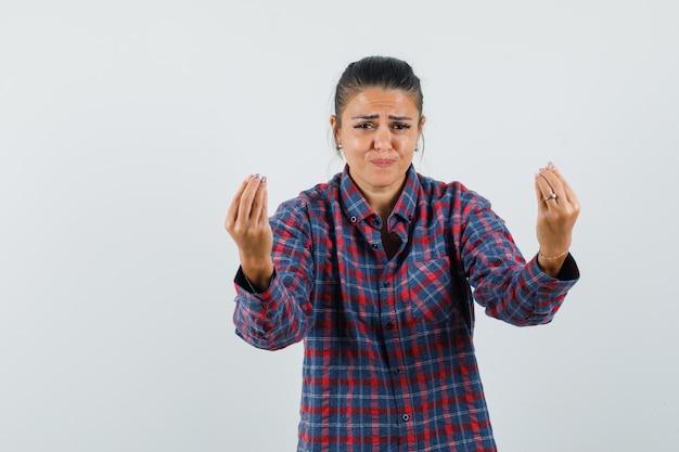 Dame doet italiaans gebaar, ontevreden met domme vraag in casual shirt vooraanzicht.
