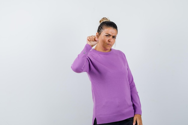 Dame dreigt met vuist in wollen blouse en kijkt hatelijk