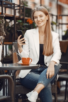 Dame drinkt een kop koffie. vrouw zit aan de tafel. meisje gebruikt een telefoon.