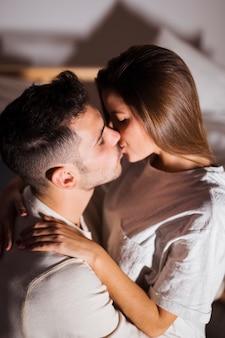 Dame en kerel die en op bed in donkere ruimte kussen koesteren
