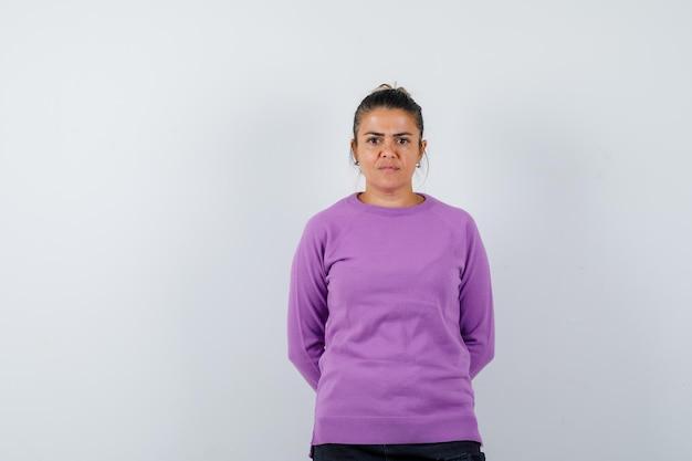 Dame hand in hand achter haar rug in wollen blouse en ziet er zelfverzekerd uit
