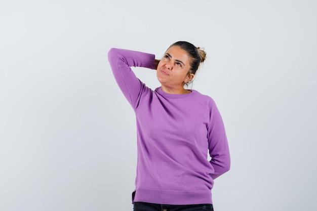 Dame houdt hand achter hoofd in wollen blouse en ziet er dromerig uit
