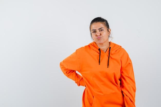 Dame houdt hand op middel, lippen gebogen, fronsend gezicht in oranje hoodie en aarzelend
