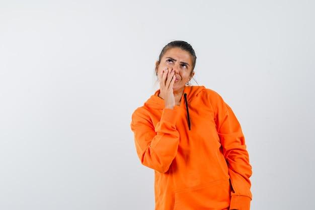Dame houdt hand op mond in oranje hoodie en kijkt peinzend looking
