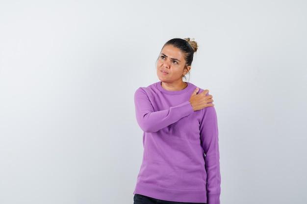 Dame houdt hand op schouder in wollen blouse en kijkt peinzend