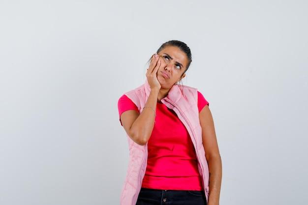 Dame houdt hand op wang in t-shirt, vest en kijkt aarzelend