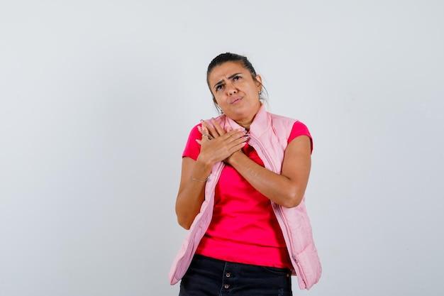 Dame houdt handen op borst in t-shirt, vest en kijkt aarzelend