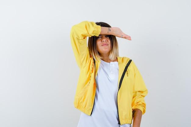 Dame houdt opgeheven arm op voorhoofd in t-shirt, jasje en kijkt beschaamd, vooraanzicht.