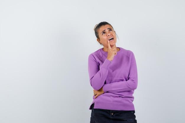 Dame houdt vinger op kin in wollen blouse en kijkt bezorgd