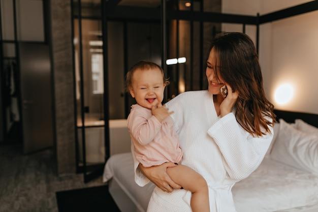 Dame in badjas in uitstekende stemming is praten over de telefoon, zittend op bed met parmantig vrouwelijke baby die haar tong toont.