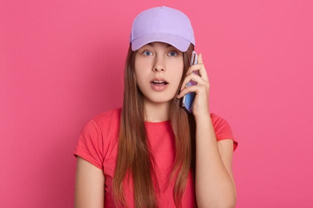 Dame in baseball cap en rode t-shirt praten via de telefoon met een verbaasde gezichtsuitdrukking
