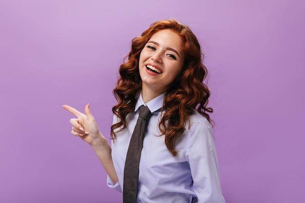Dame in blauw shirt wijst naar plaats voor tekst op paarse muur Gratis Foto