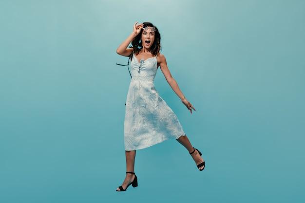 Dame in blauwe jurk neemt haar zonnebril af en springt op geïsoleerde achtergrond. verbaasde vrouw met lang haar poseren in zwarte schoenen.