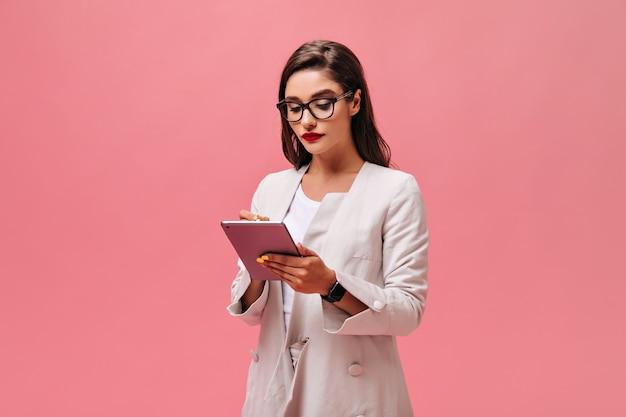 Dame in bril en jas houdt computertablet op roze achtergrond. zakenvrouw met rode lippen in lichte kleding schrijft iets.