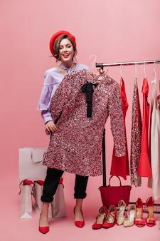 Dame in broek en blouse houdt jurk met pailletten. vrouw poseren met pakketten tijdens het winkelen op roze achtergrond.