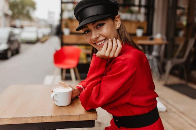 Dame in casual outfit poseren met een glimlach voor straatportret. het gelukkige glimlachende donkerbruine model drinkt thee