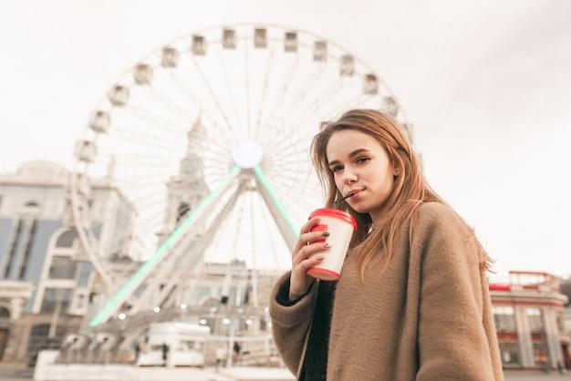 Dame in de warme lente kleding drinkt koffie op straat