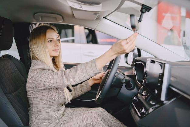 Dame in een autosalon. vrouw die de auto koopt. elegante vrouw in een bruin pak.