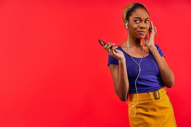 Dame in een blauw t-shirt en in een gele rok met haar verzameld in een knot met een smartphone in haar hand