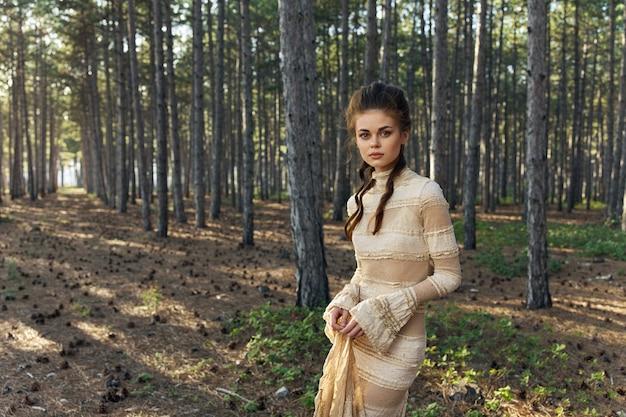 Dame in een zomerjurk met een kapsel op haar hoofd en hoge bomen aten kegels. hoge kwaliteit foto