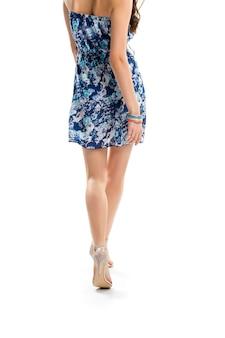 Dame in gebloemde jurk wandelen. hakschoenen van beige kleur. kledingstuk met modieuze print. lichte en aantrekkelijke kleding.