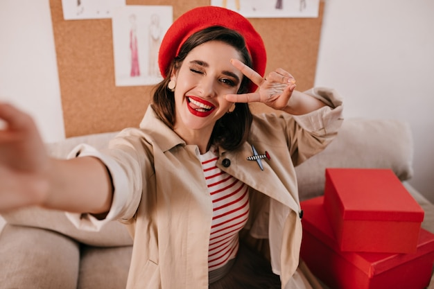 Dame in goed humeur neemt selfie, toont tong en knipoogt. leuk mooi meisje in beige jas en gestreepte trui zit op de bank.