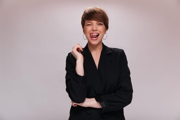 Dame in goed humeur poseren op geïsoleerde achtergrond en tong tonen. mooie vrouw in zwarte jas glimlacht op witte achtergrond