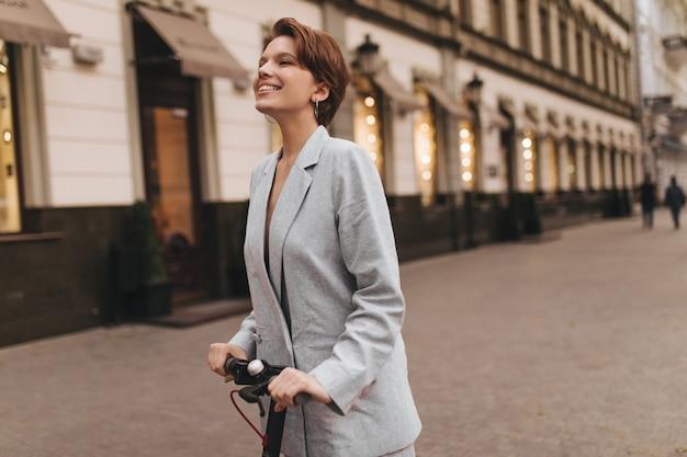 Dame in goed humeur rijdt op een scooter door de stad. gelukkig jonge vrouw in grijze oversized jas glimlacht en geniet van buiten lopen