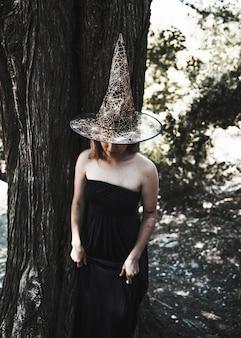 Dame in heksenkostuum die zich dichtbij boom bevinden