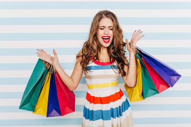 Dame in lichte zomerjurk kan emoties niet tegenhouden na succesvol winkelen in winkelcentrum. sluit portret van brunette met heldere lippen met veel pakketten op zachte witte en blauwe muur