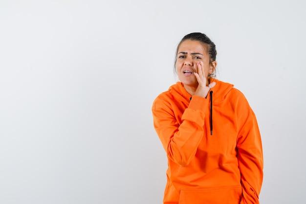Dame in oranje hoodie die geheim achter de hand vertelt en bezorgd kijkt, vooraanzicht.