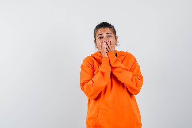 Dame in oranje hoodie die handen op de mond houdt en er opgewonden uitziet