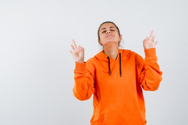 Dame in oranje hoodie die meditatiegebaar toont en er vredig uitziet