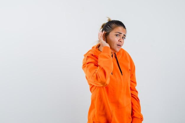 Dame in oranje hoodie die privégesprek afluistert en nieuwsgierig kijkt