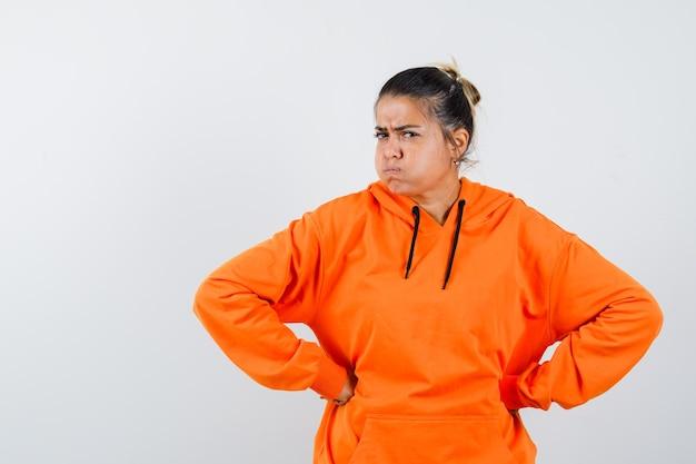 Dame in oranje hoodie hand in hand op taille en ziet er hatelijk uit