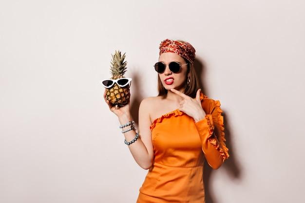 Dame in oranje jurk en zonnebril is bedachtzaam poseren en ananas op geïsoleerde ruimte te houden.