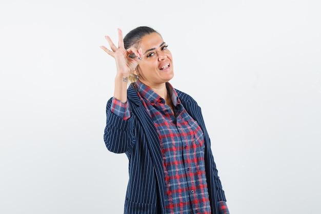 Dame in overhemd, jasje dat ok gebaar toont en vrolijk kijkt, vooraanzicht.